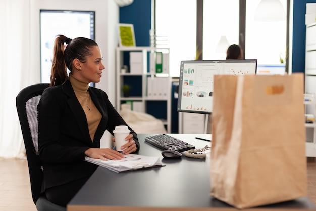Менеджер в корпоративном офисе работает на компьютере с финансовой статистикой. пакет бумажных пакетов на вынос с вкусной едой на обед на рабочем месте. сотрудник, держащий чашку кофе.