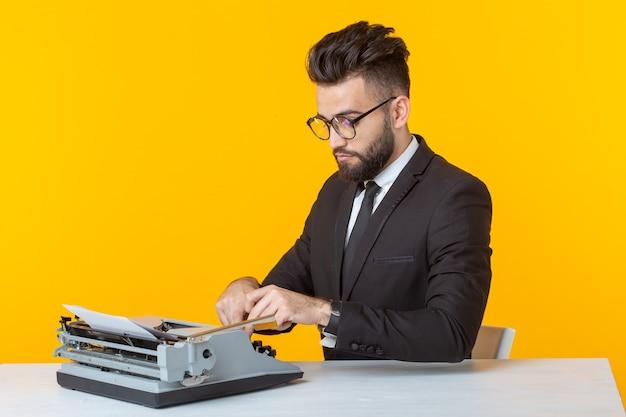 黄色い壁のタイプライターでテキストを入力するフォーマルスーツのマネージャー