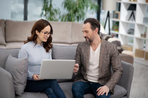 Менеджер мебельного магазина показывает модели на своем ноутбуке