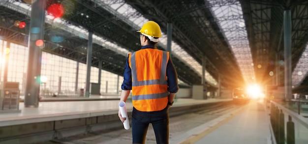 Менеджер промышленного инженера, держащего чертежи и проверки структуры и строительной железнодорожной площадки