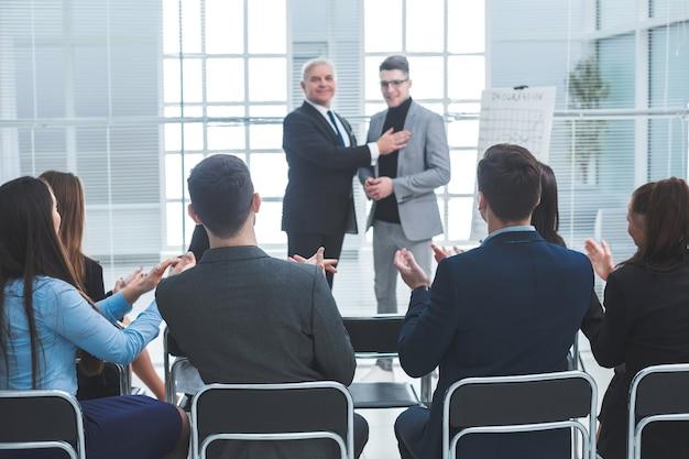 マネージャーは、ビジネスチームとの会議で会社の新入社員を紹介しています。