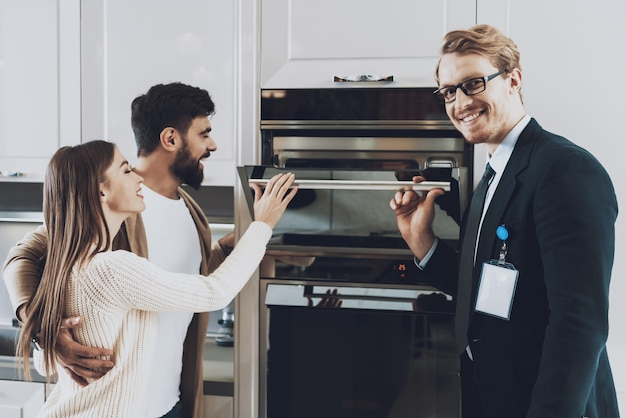 Manager is showing built-in stove to couple clients.