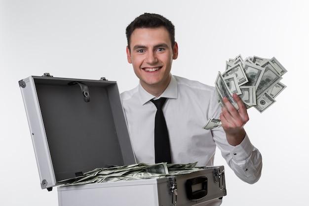 관리자는 돈으로 가득 찬 가방을 가진 돈 남자에게서 발길질합니다.