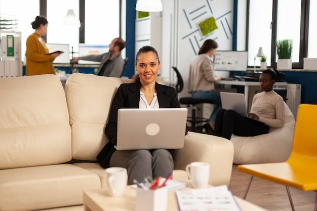 Manager lady writing on laptop looking at camera smiling while diverse colleagues working in background