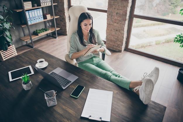 現代のレンガ造りのロフトでコピーブックにメモを書くマネージャーの女性
