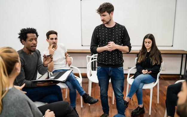 オフィスのクリエイティブデザイナーのグループとのブレーンストーミングミーティングを率いるマネージャー。リーダーとビジネスコンセプト