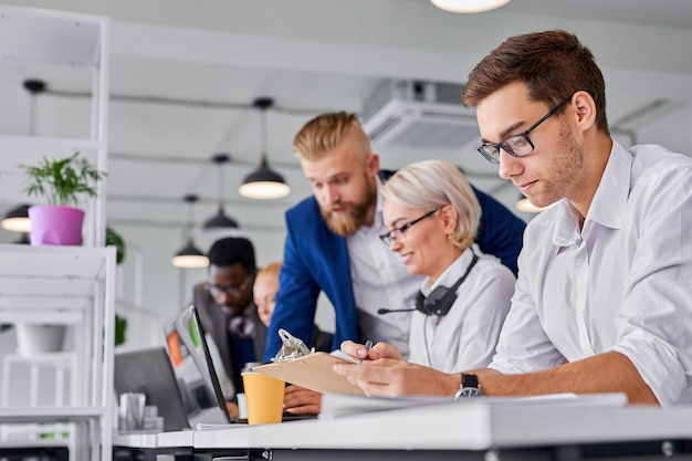 관리자 남성은 사무실에서 일하고 백인 남자는 집중된 종이를보고 생각하고 다른 사람들은 함께 일하고 남자에게 집중합니다.
