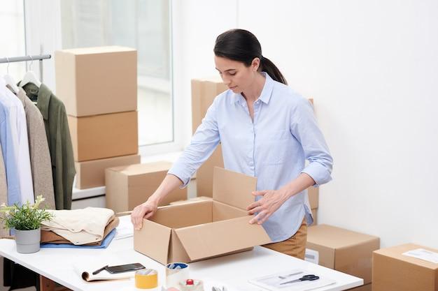 オンラインショップのマネージャーは、クライアント用の新しいカジュアルウェアを梱包してそこに置く前に空の箱を開けます