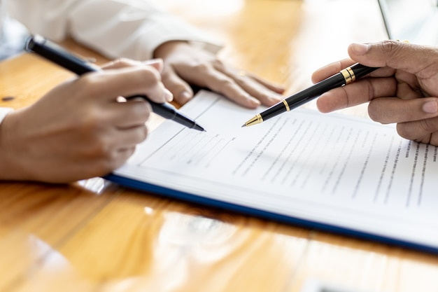 The manager points to the employment contract for the applicant to sign as an agreement to work, the applicant signs the contract to work with the company, the salary agreement and benefits.