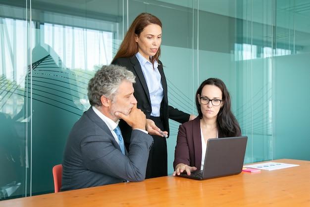 Manager che presenta il progetto ai colleghi pensierosi.