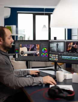 Manager production editing video project working in start up creative agency office at pc with two monitors