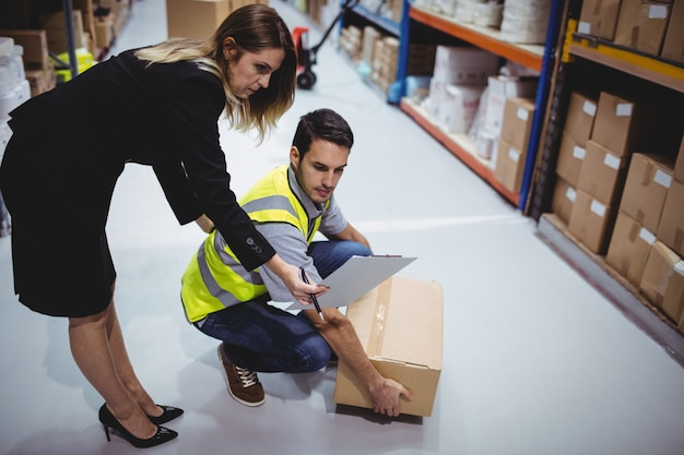 Manager showing clipboard to worker in warehouse
