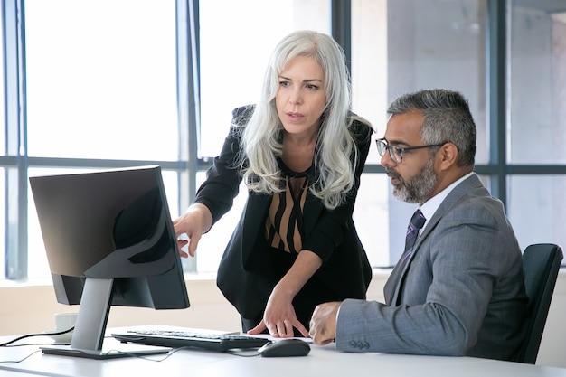 상사에게 프레젠테이션 세부 정보를 보여주는 관리자. 두 동료 컴퓨터 모니터에서 콘텐츠를 논의하고, 디스플레이를 가리키고, 파노라마 창으로 직장에서 이야기. 비즈니스 커뮤니케이션 개념