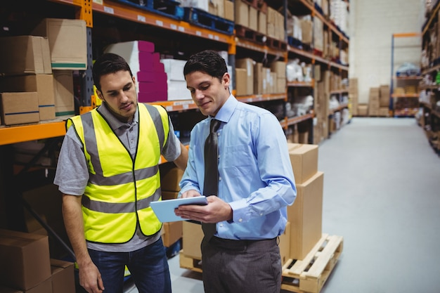 Manager showing tablet to worker in warehouse
