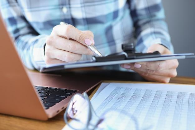 マネージャーは自分の机に座って、ペンで書類を持っています。ビジネス戦略計画の概念