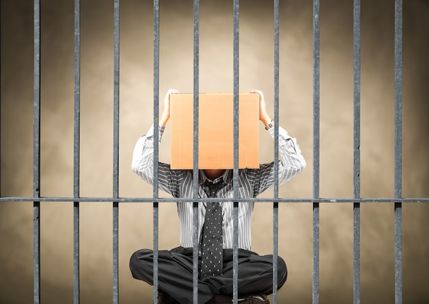 Manager sitting behind the bars of a prison with his head inside a box