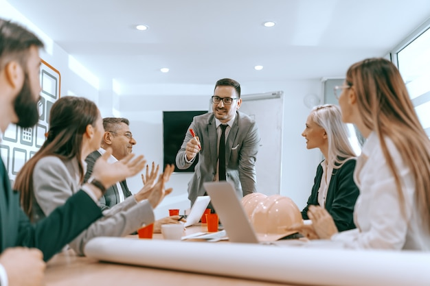 立っていると役員室で従業員と話しているマネージャー。建築家のビジネスコンセプト。組合には強さがあります。