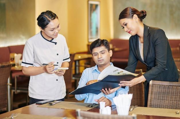 Менеджер предлагает фирменное блюдо гостю
