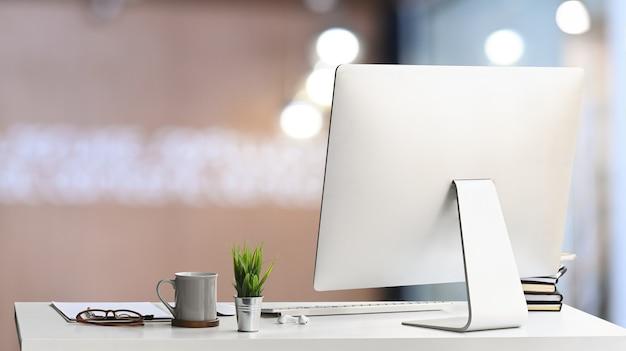 Стол менеджера с компьютером и канцелярскими принадлежностями в современном офисе.