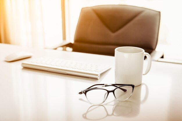 Manager table with desktop computer and eye glasses