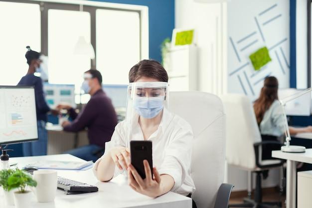Manager che utilizza lo smartphone per la conferenza online indossando la maschera facciale contro il covid-19 come precauzione di sicurezza