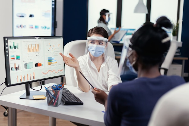 アフリカの従業員に財務グラフを説明するcovid19のフェイスマスクを着用したマネージャー。コルとの世界的大流行のために社会的距離を尊重する新しい通常の会社で働く多民族チーム