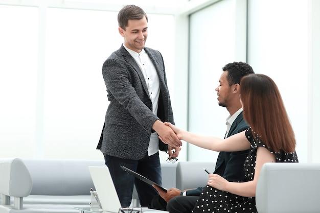 Менеджер встречает клиентов в холле банка. фото с копией пространства