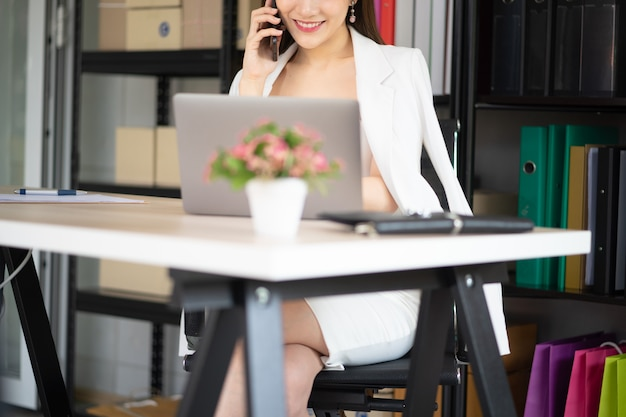 A manager, in white dress, is sitting in office. she is calling to customer to commit a bu