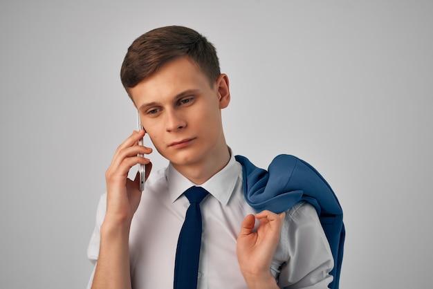 電話の専門家の仕事で話している彼の肩にジャケットを着たマネージャー