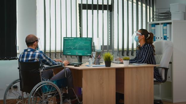 新しい通常の営業所で働く保護マスクを持った職場で車椅子に来る障害のあるマネージャー。社会的距離を尊重する金融会社の固定化されたフリーランサー。