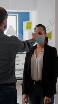 Manager with protection face mask examines collegues temperature with infrared thermometer before en...
