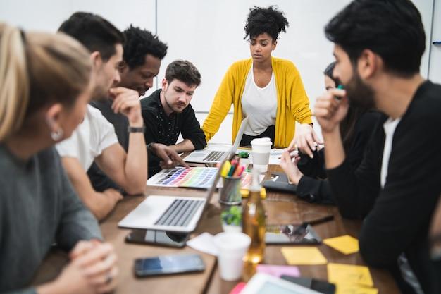 사무실에서 창의적인 디자이너 그룹과 브레인 스토밍 회의를 선도하는 관리자 여자. 지도자와 비즈니스 개념.