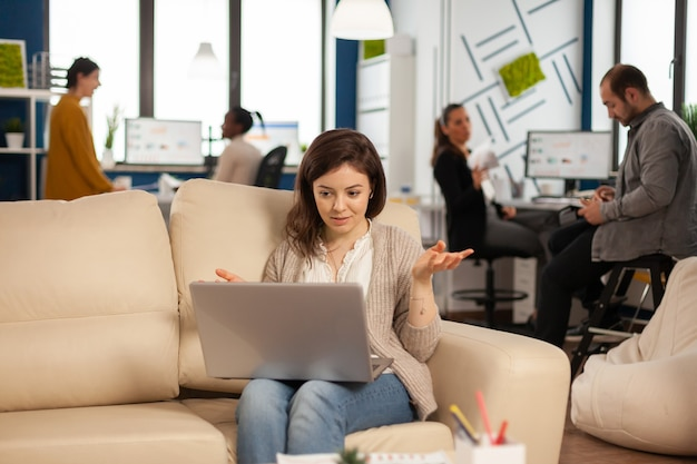 Manager woman sitting on couch holding laptop and talking on video call during virtual conference working in business modern office