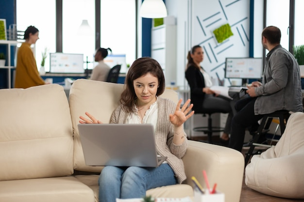 Manager woman sitting on couch holding laptop and talking on video call during
