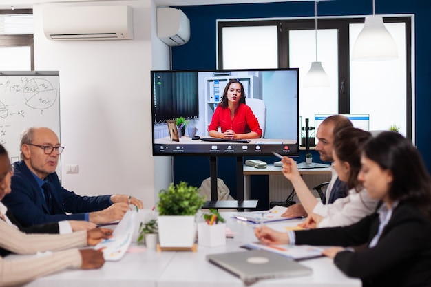 仮想会議の作業中にビデオ通話で話している正面の前に座っているマネージャーの女性