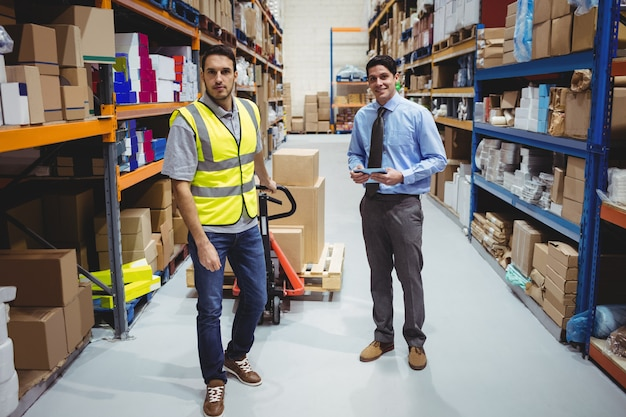Manager and worker pulling trolley in warehouse