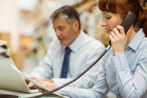 관리자는 노트북에서 작업하고 책상에서 전화 통화