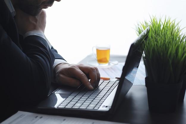マネージャーはオフィスのラップトップで働いています。ビジネスマンはオンライン取引を行います。インターネットを介した取引所での取引。
