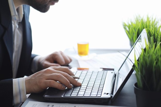 Manager works at a laptop in the office. businessman makes an online transaction. trading on the exchange via the internet.