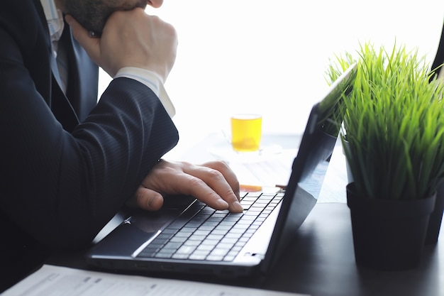 Manager works at a laptop in the office businessman makes an online transaction