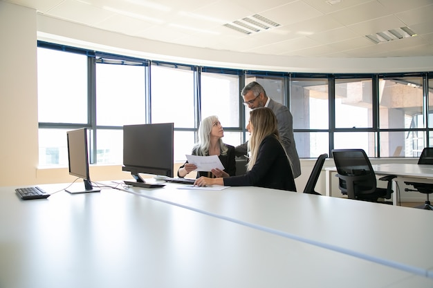 Managers discussing reports with boss, sitting at meeting table with monitor and holding documents. business meeting or teamwork concept