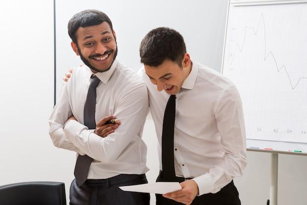 マネージャーは、オフィスで成功した男性のビジネスマンを笑顔で成功を楽しんだ