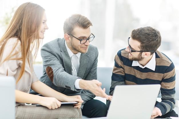 Менеджеры компании и клиент обсуждают условия нового контракта и смотрят на ...