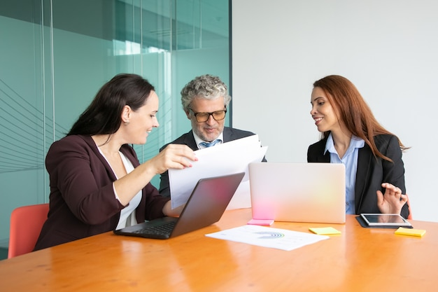 上司に紙のレポートを提示するマネージャー。スーツの灰色の髪の男と2人のビジネス女性が一緒に論文をレビューします。