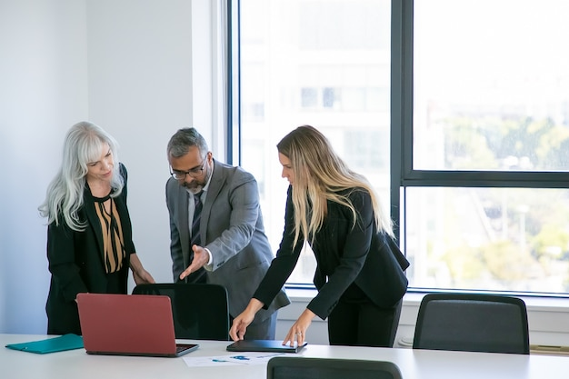 Менеджеры показывают презентацию проекта боссу. бизнесмен указывая рукой на экран ноутбука и разговаривая с коллегами-женщинами. широкий план. концепция делового общения