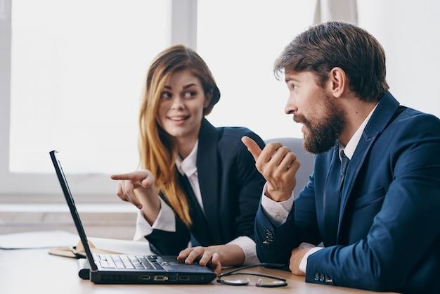 Менеджеры, сидящие перед профессионалами совместной работы ноутбука