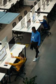 Менеджеры работают за компьютерами, рабочее место в it-офисе. профессиональная командная работа и планирование, групповой мозговой штурм, современный интерьер компании на заднем плане