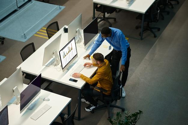 관리자는 컴퓨터, it 사무실의 직장에서 일합니다. 전문적인 팀워크 및 계획, 그룹 브레인스토밍, 배경에 대한 현대적인 회사 내부