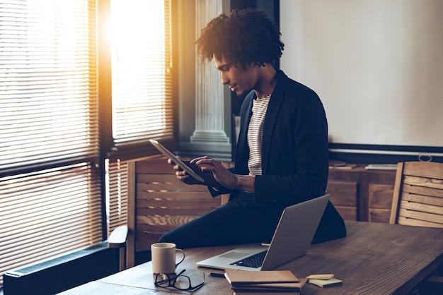 Управление его расписанием. вид сбоку молодого красивого африканца, использующего свой цифровой планшет