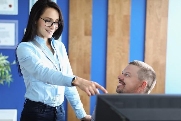 コンピューターの画面で男性に指を向ける女性を管理します。プログラミングコースの概念